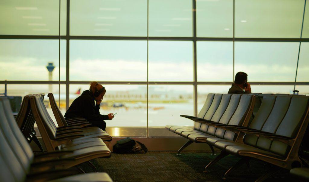 Pessoa sentada na sala de embarque de aeroporto.