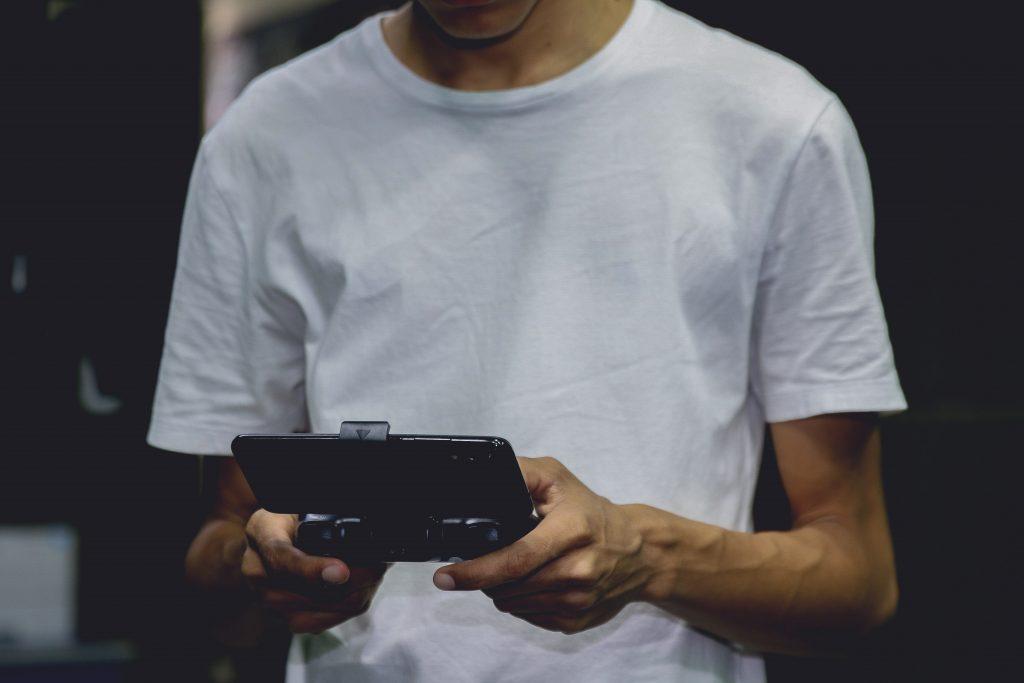 Imagem mostra um homem manuseando um console portátil.