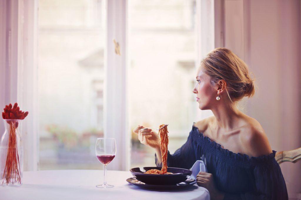 Mulher sentada a mesa comendo macarrão e bebendo uma taça de vinho.
