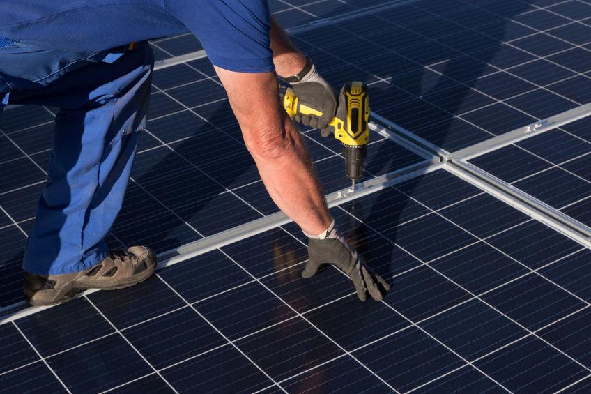 Imagem mostra um homem usando uma parafusadeira DeWalt em um painel solar.