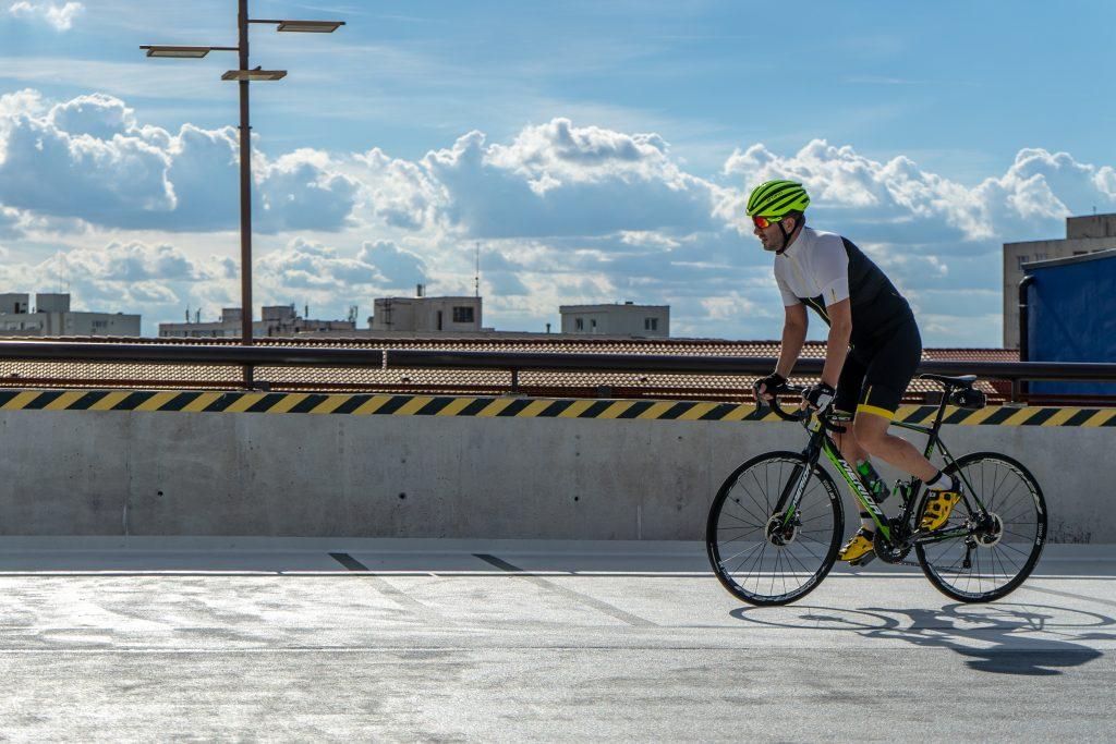 Imagem mostra um ciclista devidamente equipado pedalando por uma via asfaltada. Ao fundo, é possível ver uma breve skyline de uma cidade.
