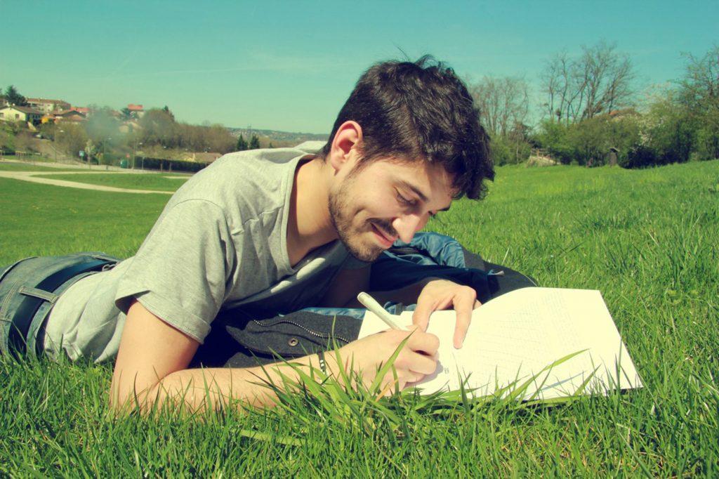 Na foto um homem deitado em um gramado escrevendo em um caderno.