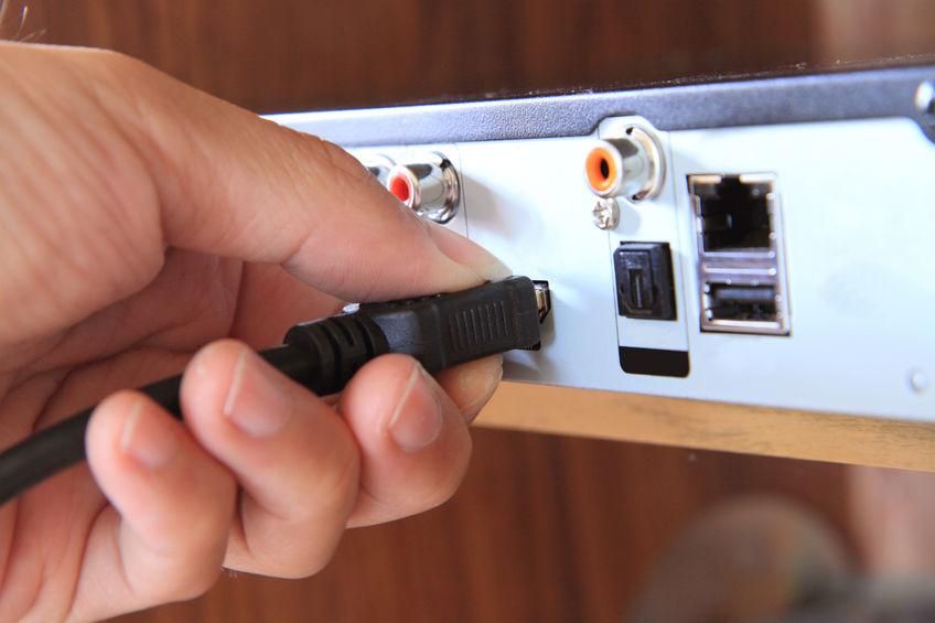 Mão conectando cabo Hdmi.