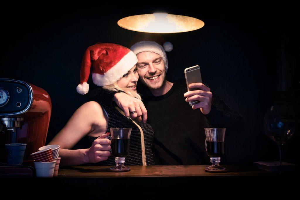 Na foto um casal tirando fotos usando gorros de Papai Noel.
