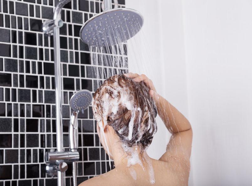 Uma mulher lavando o cabelo no banho