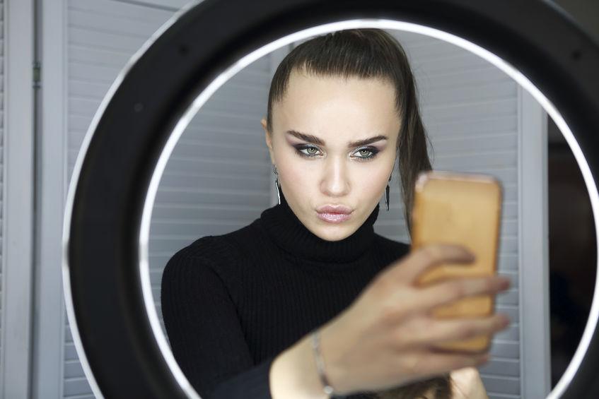 Mulher tirando selfie com celular e um ring light.