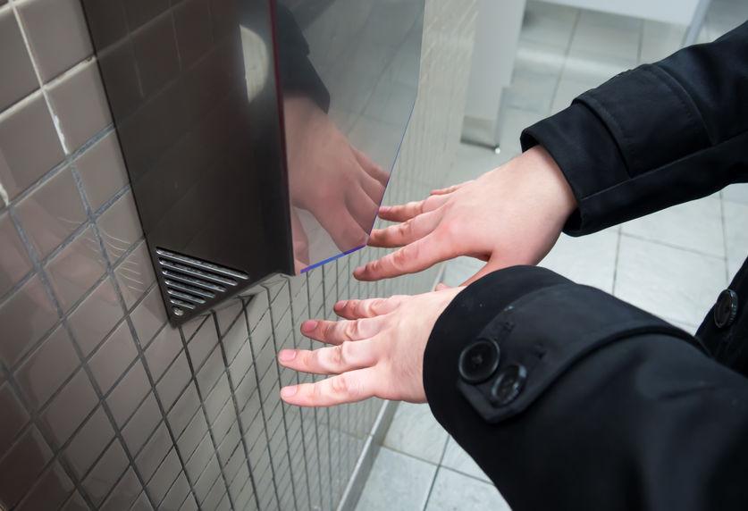 Pessoa seca as mãos em secador de banheiro