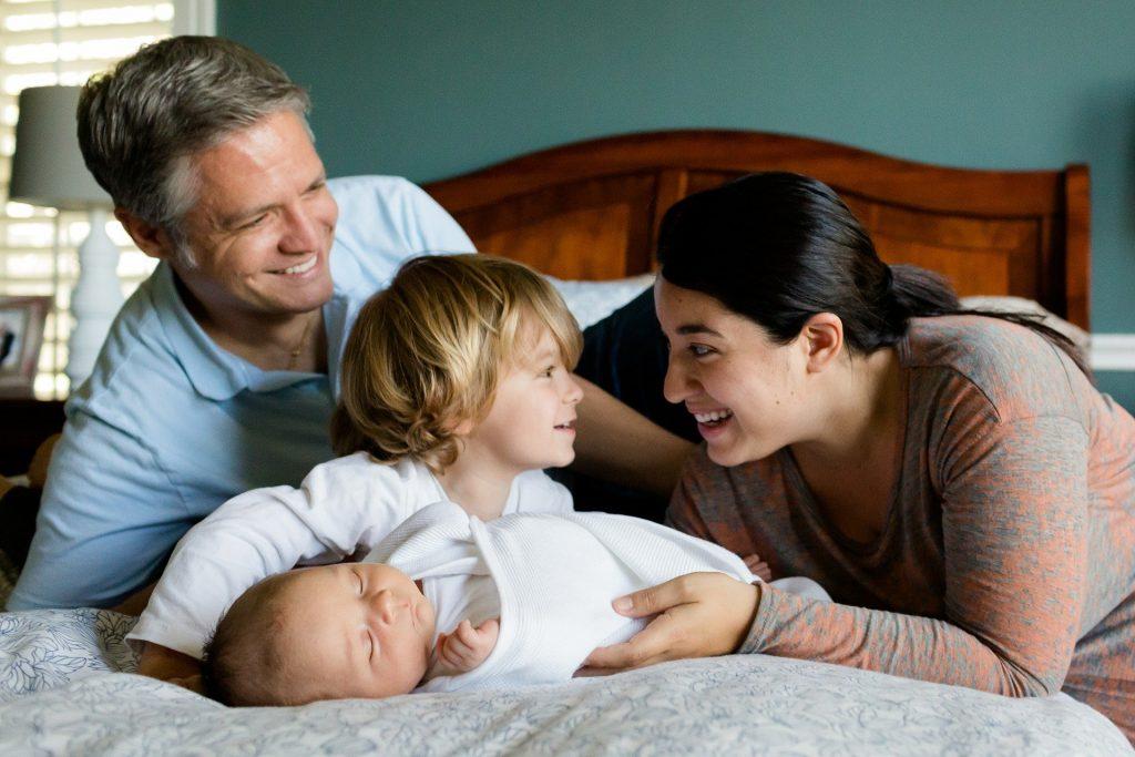 Mãe, pai e dois filhos crianças deitados na cama.