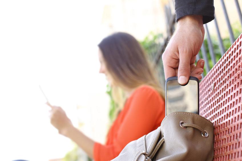 Ladrão furtando celular de bolsa enquanto mulher está distraída em banco de praça