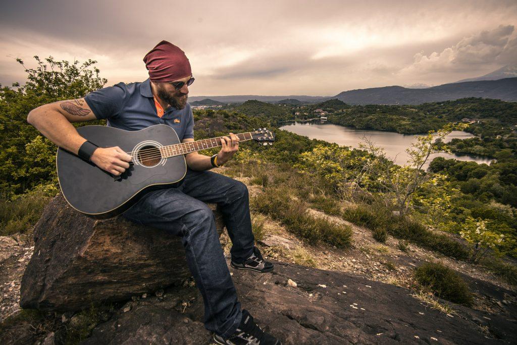 Na foto um homem sentando em uma pedra com um violão.