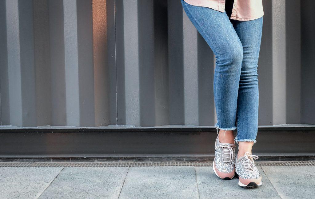 Foto que mostra da cintura para baixo de uma mulher de calça jeans e tênis esportivo, encostada em uma parede cinza.
