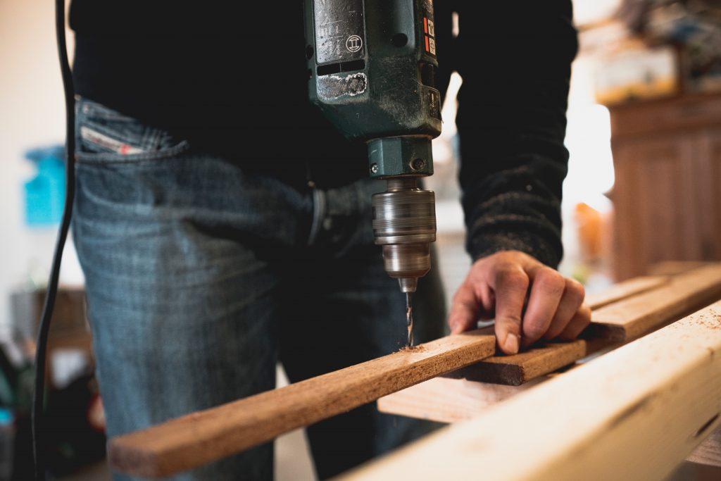 Imagem mostra um homem usando uma furadeira em uma tábua.