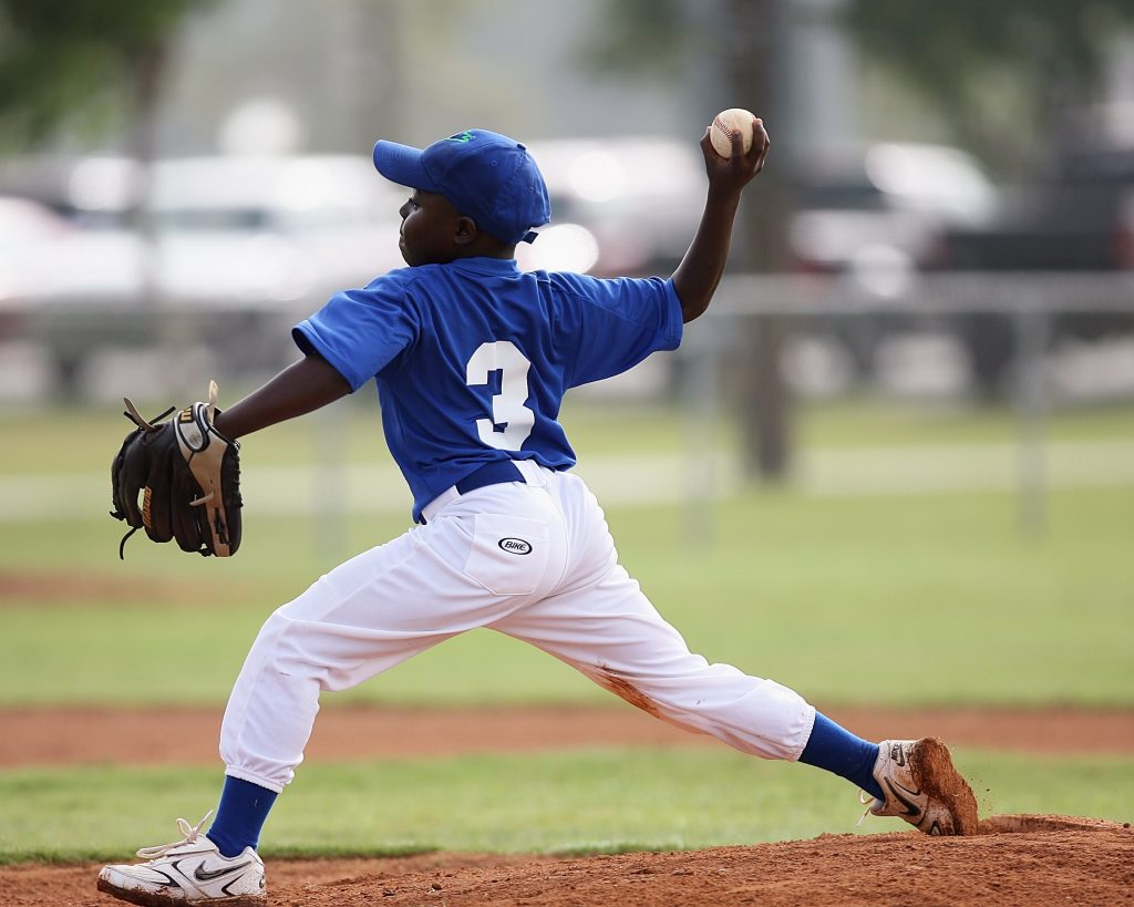Imagem mostra o momento em que uma criança arremessa a bola, com o braço direito arqueado, o esquerdo fazendo apoio e as pernas flexionadas.