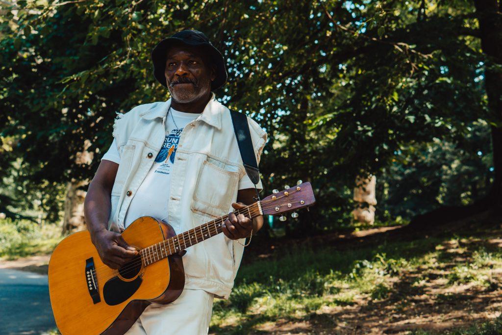 Imagem mostra um homem tocando violão na esquina de uma rua intensamente arborizada.