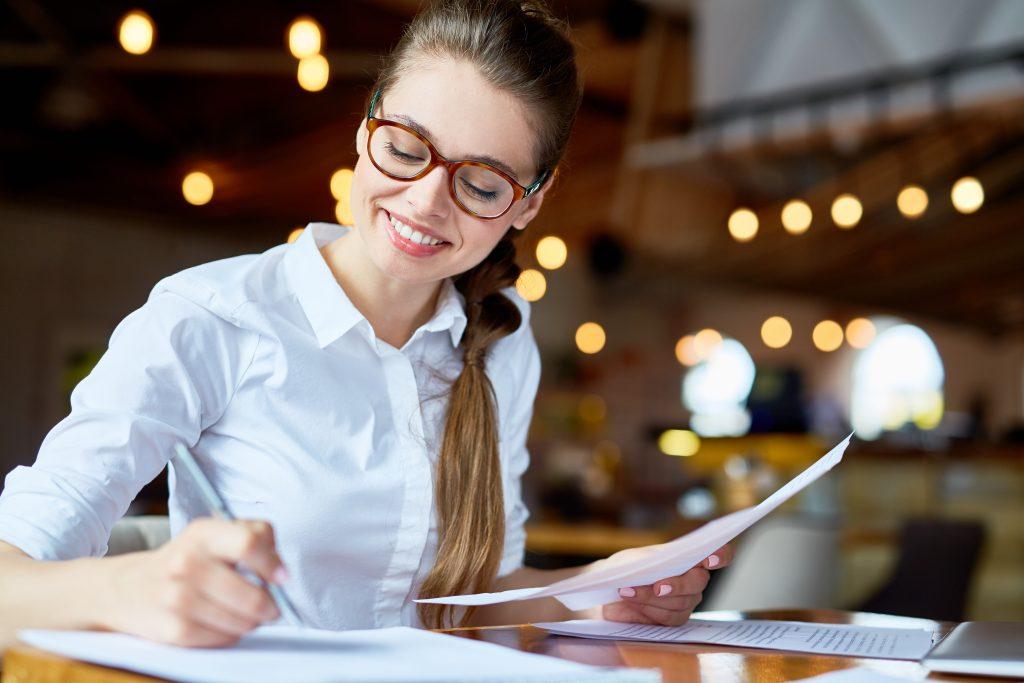 Imagem de mulher escrevendo em uma folha.