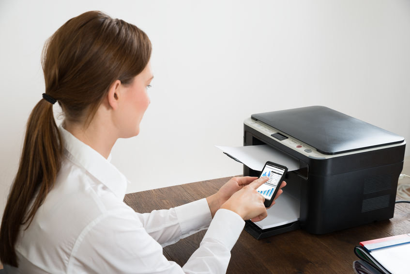 Mão segurando celular e impressora ao fundo.