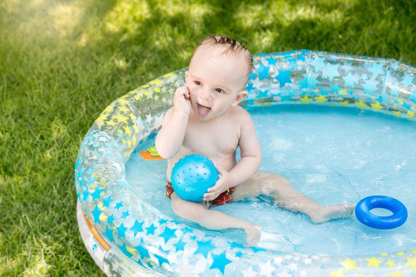 Na foto um bebê dentro de uma banheira inflável.