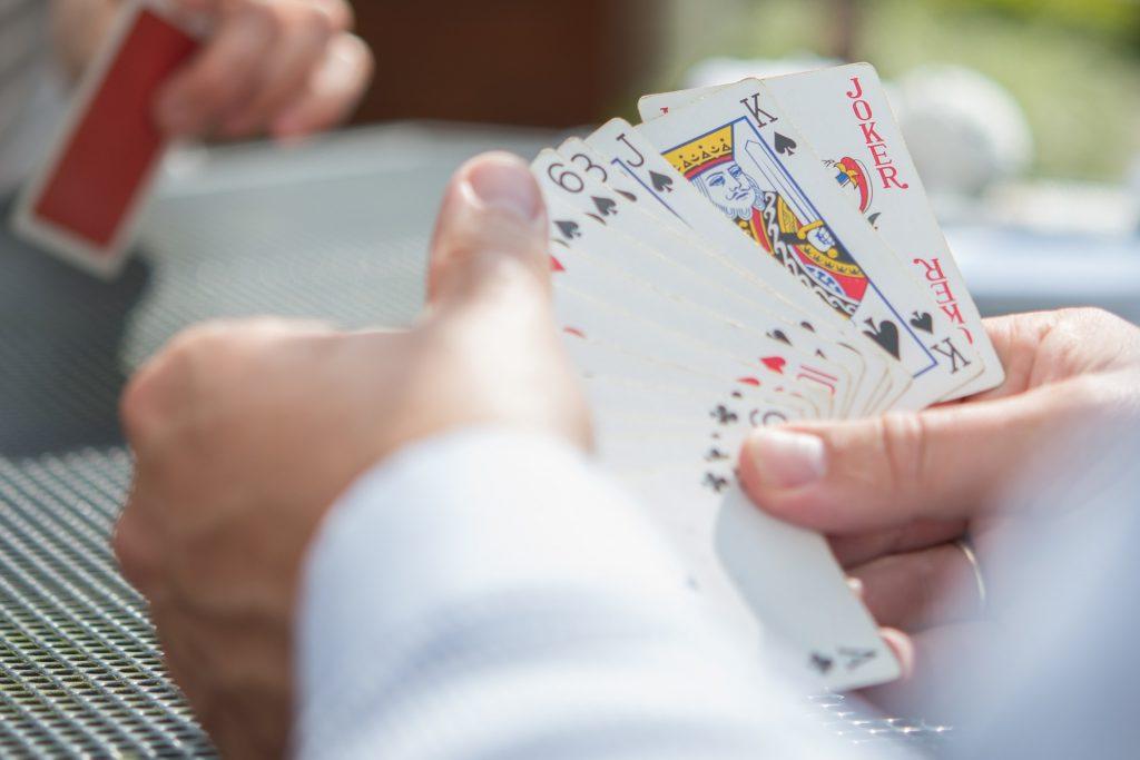 Imagem mostra uma mão segurando uma série de cartas, com seus naipes à mostra para a câmera