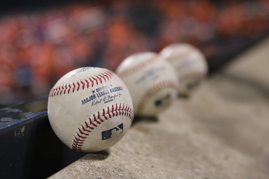 Imagem mostra três bolas oficiais da MLB enfileiradas. A primeira está focada, as outras duas, em segundo plano, desfocadas.
