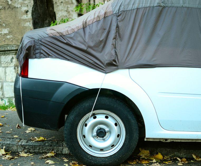 Carro vermelho semi coberto com capa para carro.
