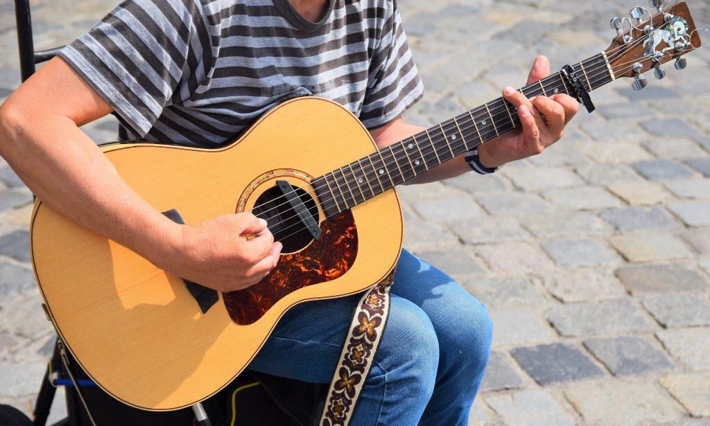 Imagem mostra uma pessoa tocando violão sentada numa cadeira, posicionada num calçadão. O foco está centrado no violão e seu captador.