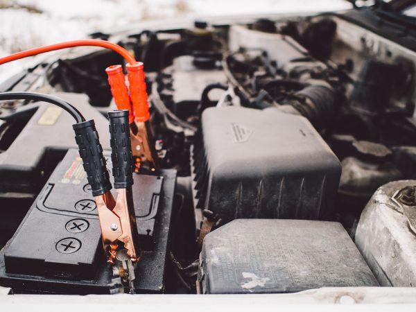 Imagem mostra uma bateria automotiva sendo carregada com cabos.