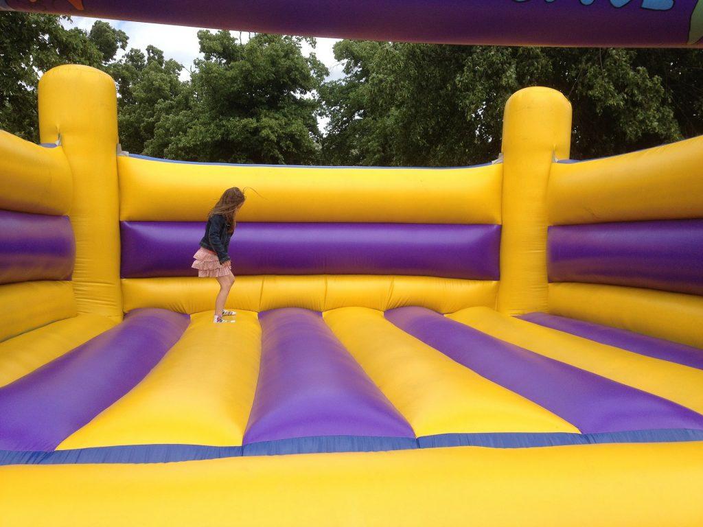 Menina pula sozinha em castelo inflável gigante nas cores roxo e amarelo
