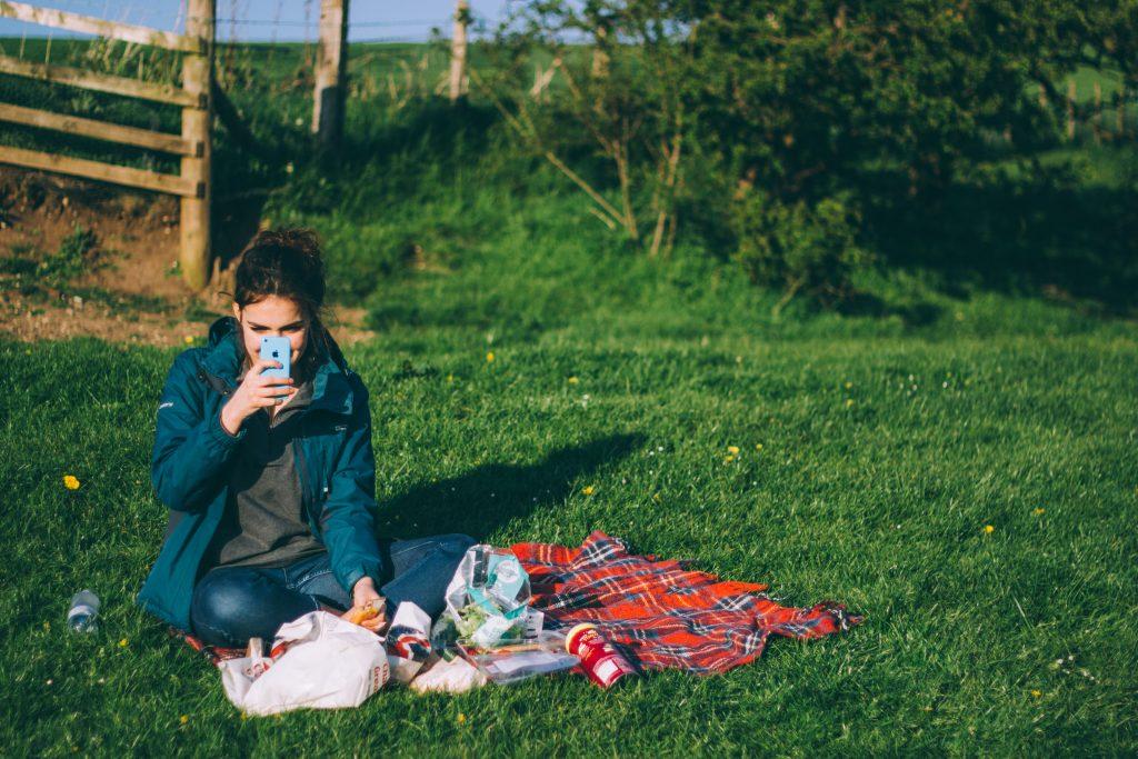 Imagem mostra uma mulher usando o telefone celular em uma área de piquenique.