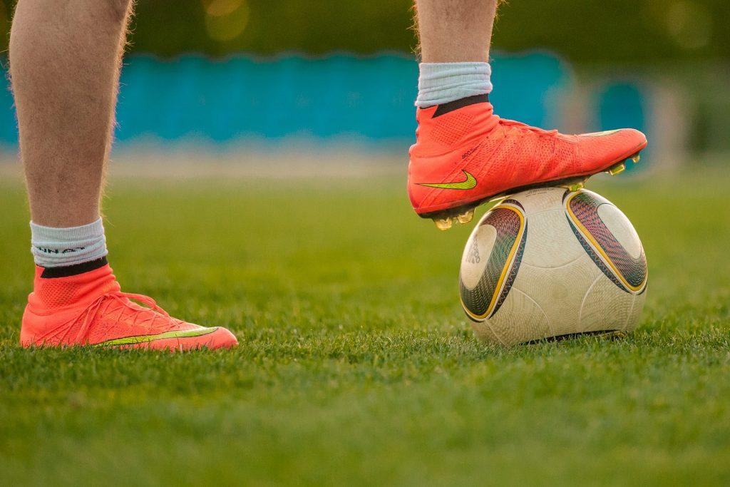 Imagem mostra somente os pés de uma pessoa, calça chuteira Nike. Seu pé direito se apoia no gramado, enquanto o pé esquerdo está apoiado numa bola.