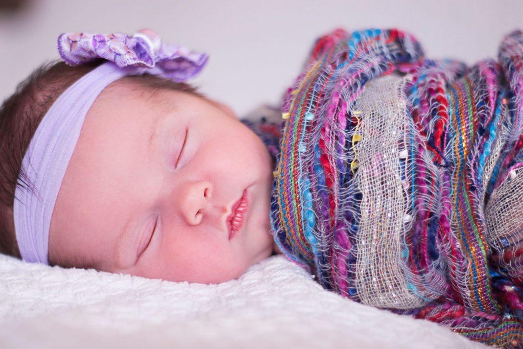 Na foto uma bebê dormindo.