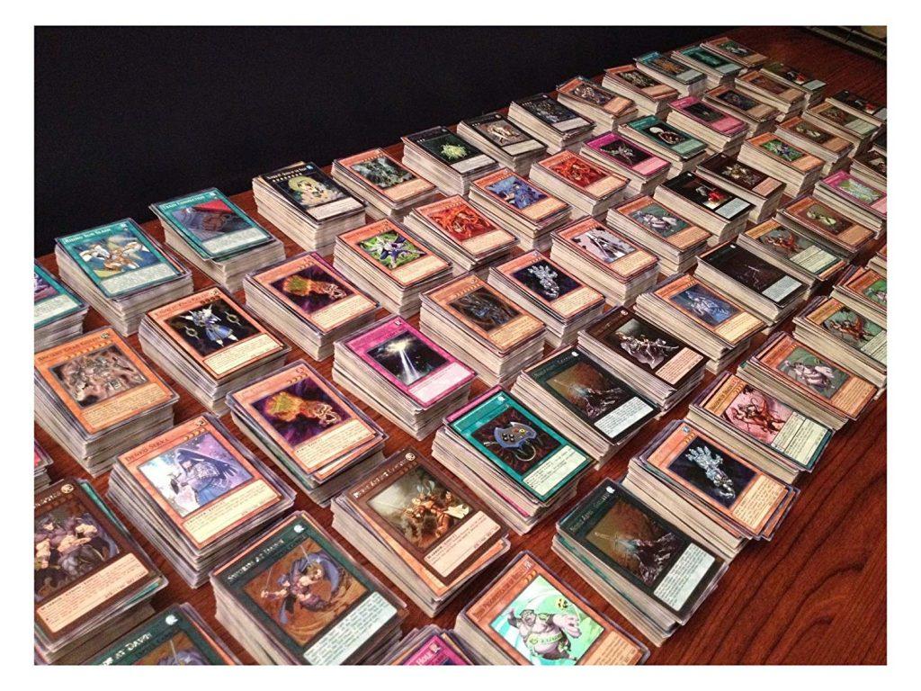 Vários montes de cartas de deck Yugioh estão espalhados em cima de uma mesa de madeira.