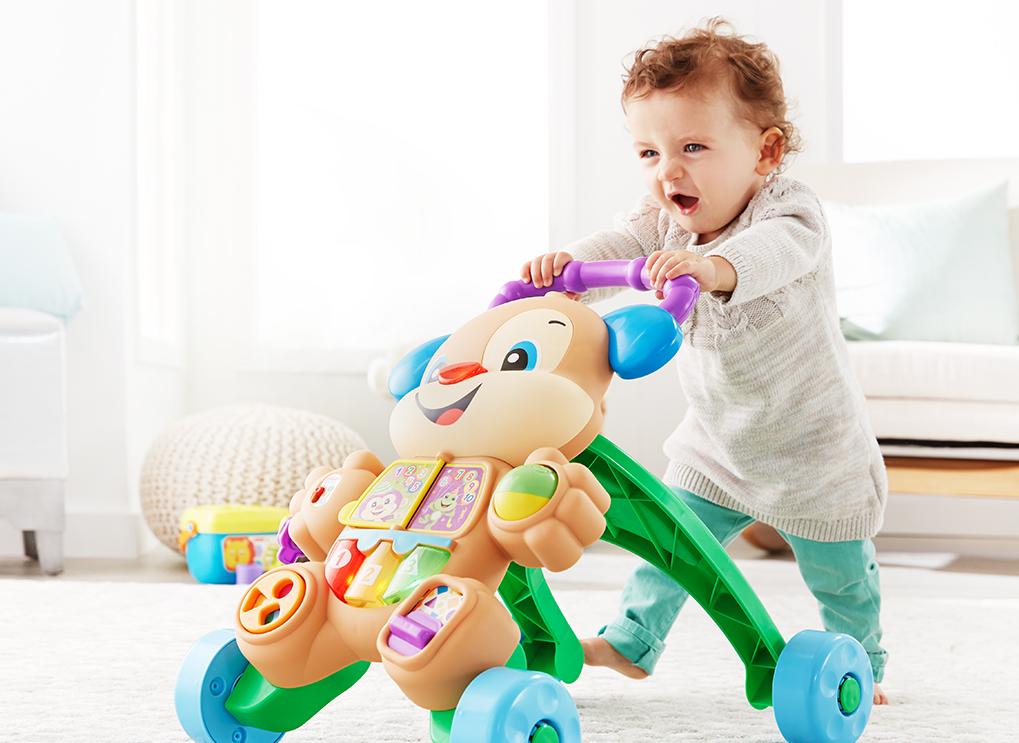 Na foto um criança empurrando um brinquedo em formato de urso.