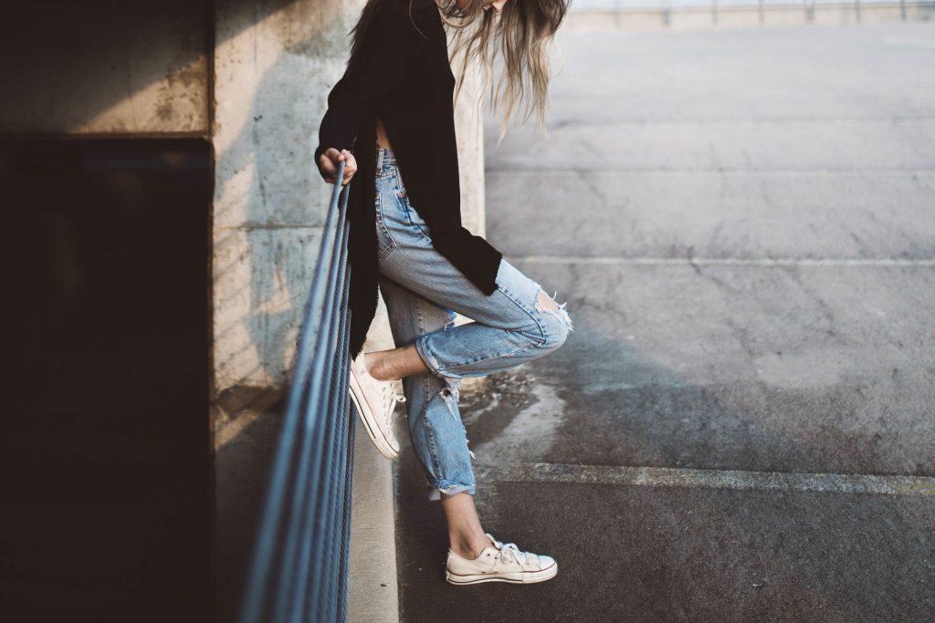 Mulher de perfil encostada em grade vestindo blusa preta, calça jeans e all star.