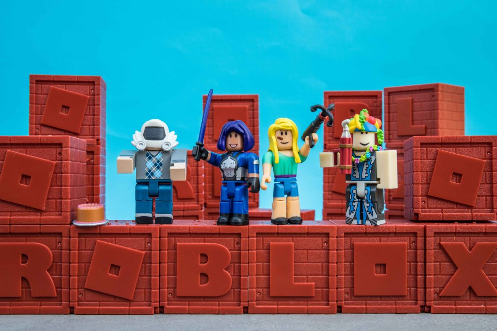 Na foto quatro bonecos Roblox em cima de cubos que imitam tijolo.