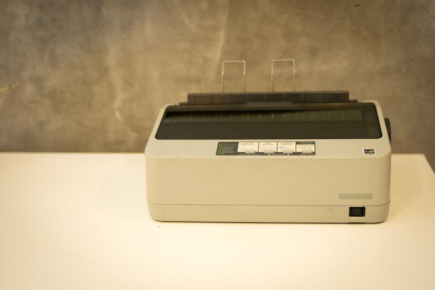 A imagem mostra uma impressora matricial imprimindo um papel