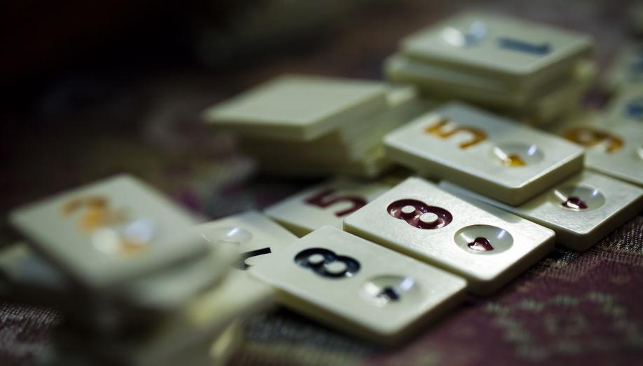 Imagem mostra um monte de peças de Rummikub, com foco seletivo em duas peças de número oito.