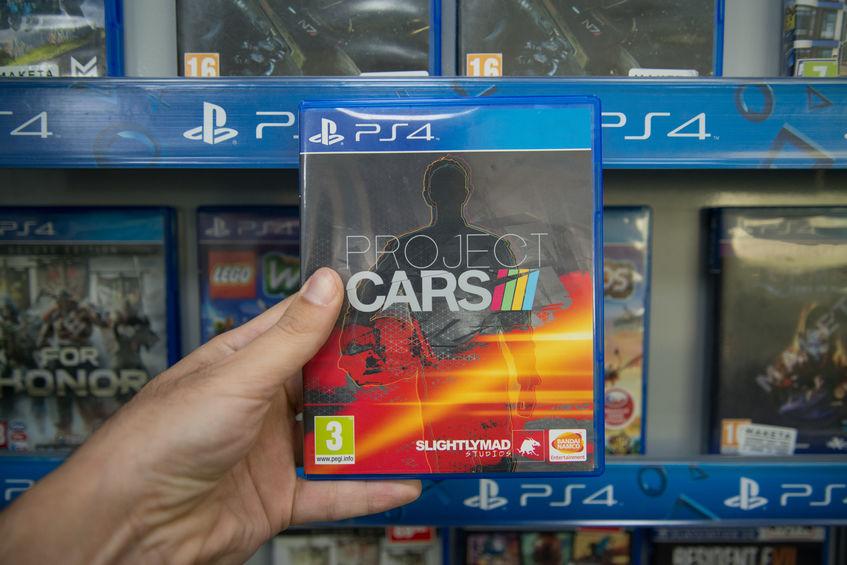 Imagem mostra uma mão segurando a caixa de um jogo de PS4 em frente à uma prateleira com outros jogos.