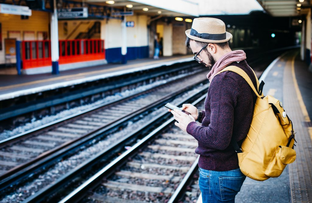 Homem na estação de trem, lendo no celular.