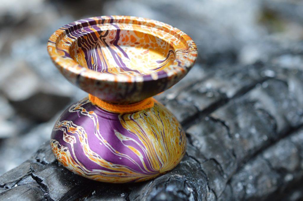 Um ioiô borboleta colorido está em cima de uma superfície que parece um tronco de árvore.
