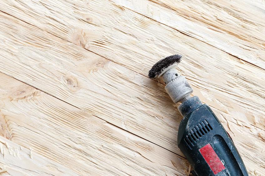 Imagem mostra uma micro retífica com uma escova na ponta sobre uma superfície de madeira.