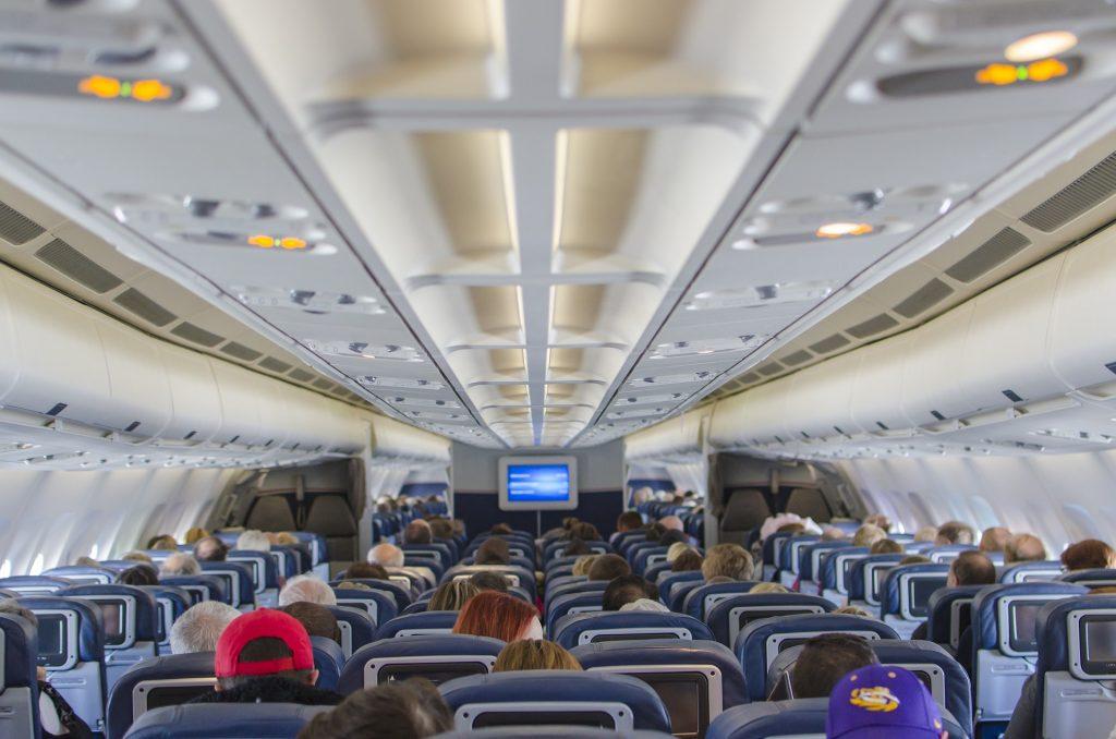 Visão interna de um avião com passageiros.