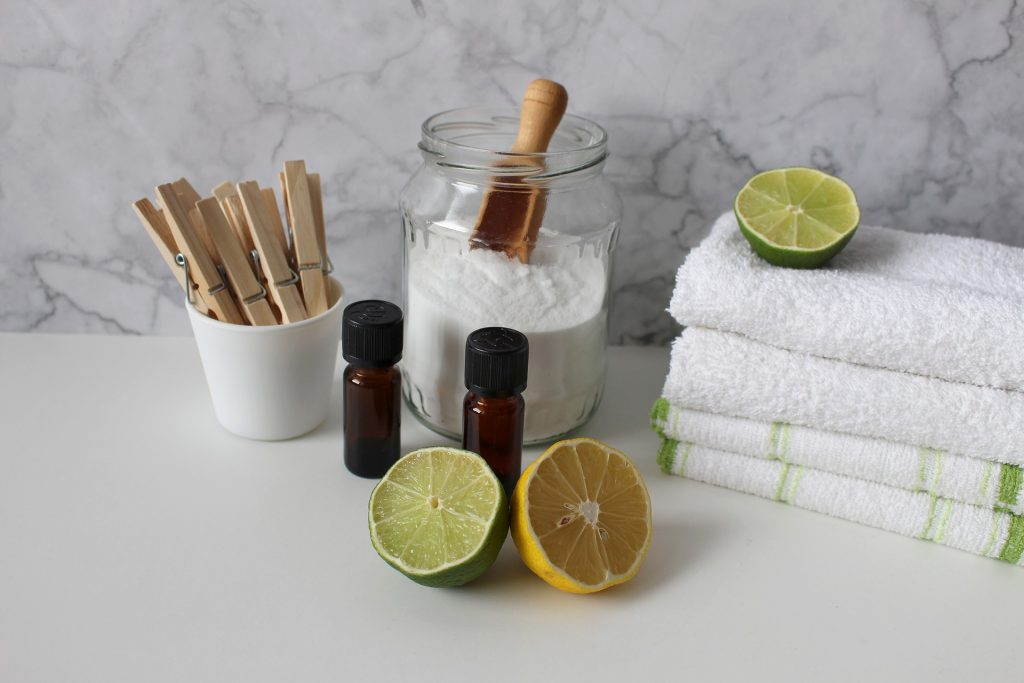 Imagem de óleo de limão, limões cortados, toalhas e produtos de limpeza