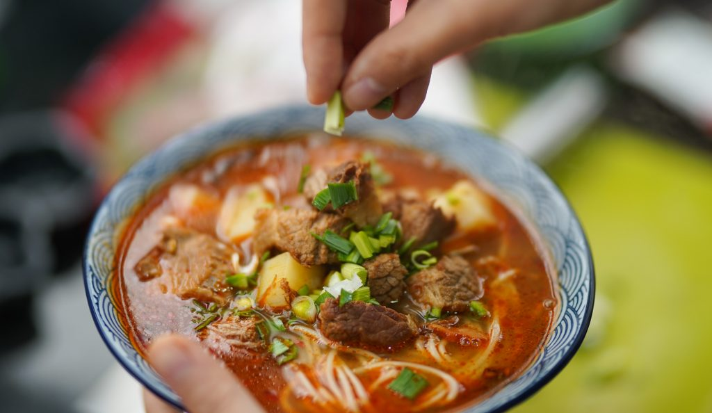 Tigela de sopa de carne e legumes na mão de uma pessoa.