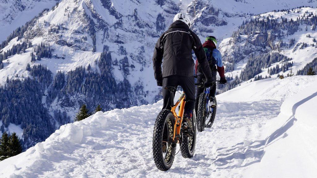 Imagem mostra pessoas pedalando em uma montanha coberta de neve.
