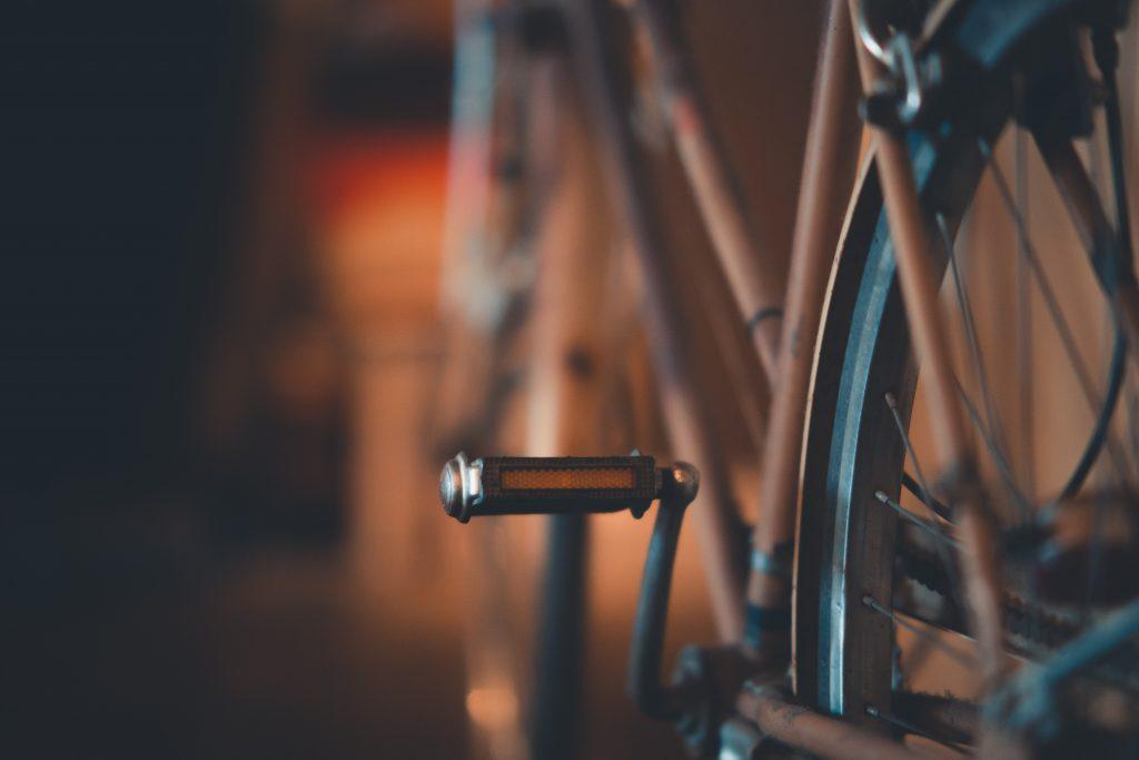 Imagem mostra um pedal do tipo plataforma no foco seletivo, com o restante da bicicleta desfocado ao fundo.