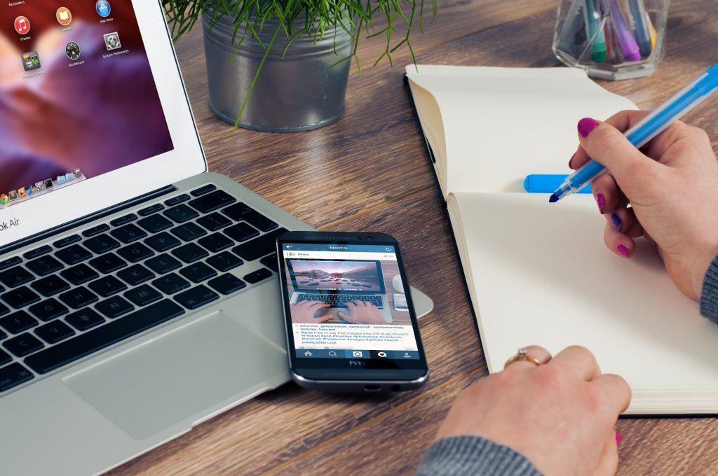 Na foto uma pessoa escrevendo em um papel em frente a um notebook.