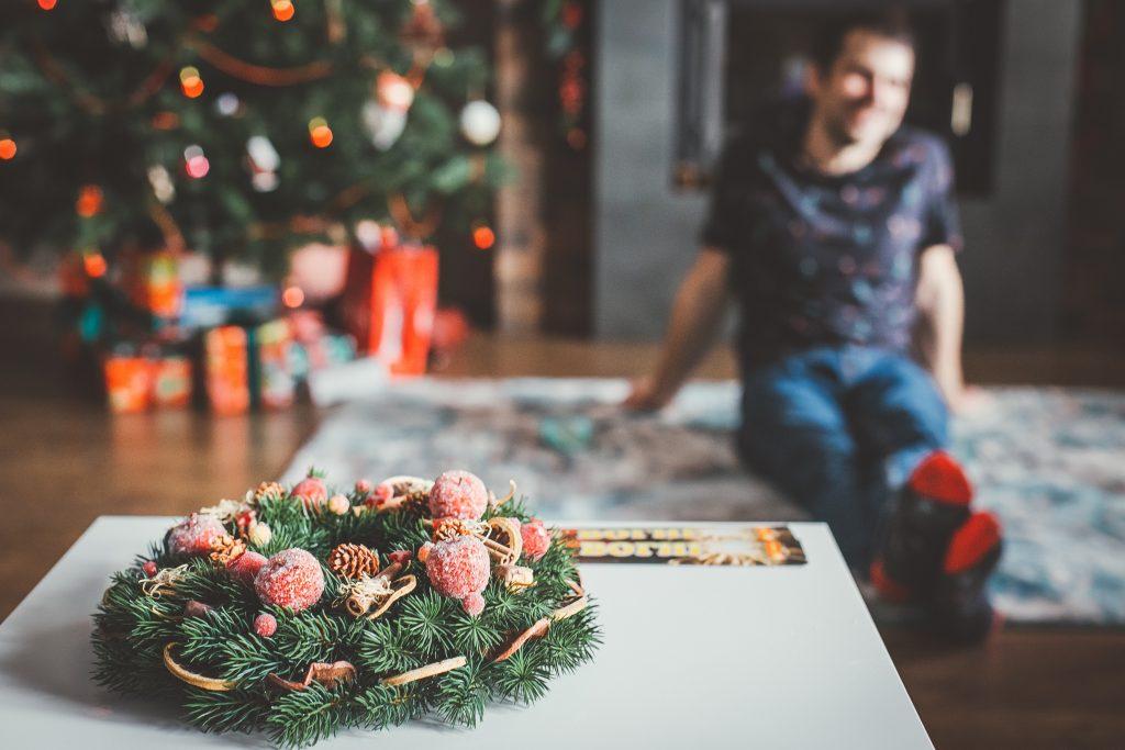 Na foto um presente e atrás um homem sentado ao lado de uma árvore de Natal.