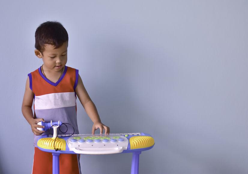 Menino tocando teclado infantil.