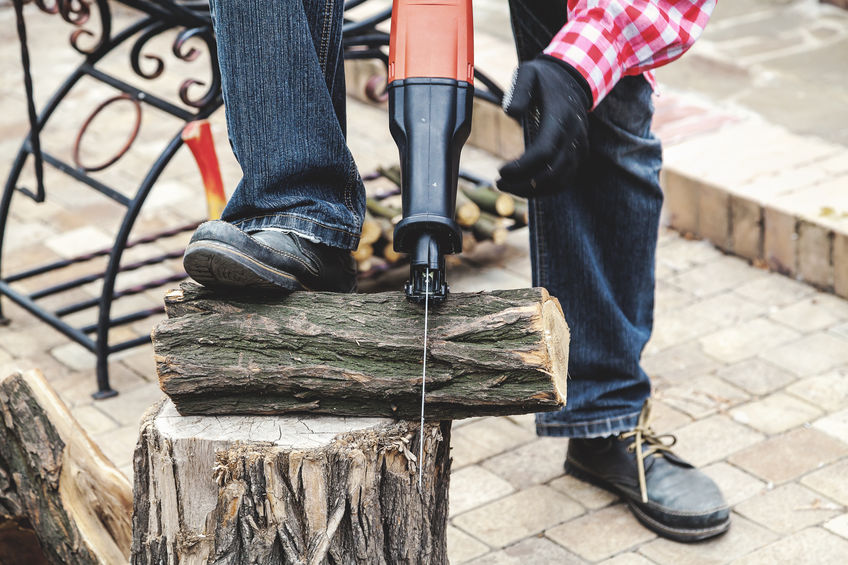 Imagem mostra uma pessoa usando uma serra sabre para cortar um pedaço de lenha.