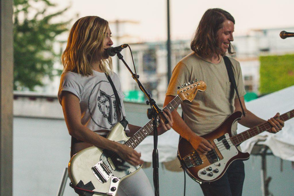 Uma mulher (à esquerda) toca uma guitarra enquanto canta no microfone, conectado a um cabo, enquanto um homem (à direita) toca um baixo em ambiente externo.